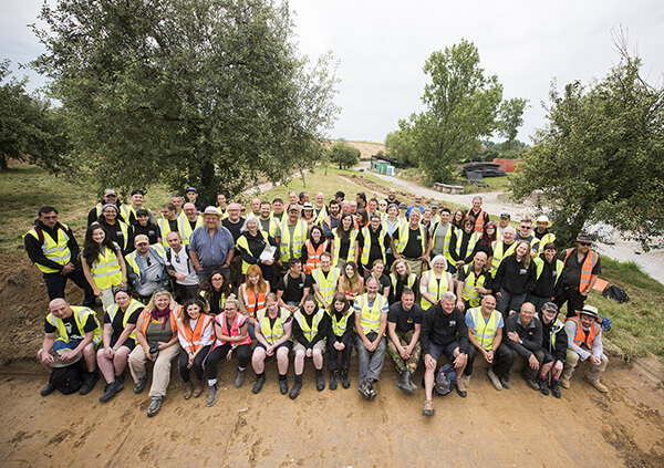 Group shot of the entire 2019 excavation team, posing in the orchard of Mont Saint Jean in Belgium, wearing high vis jackets