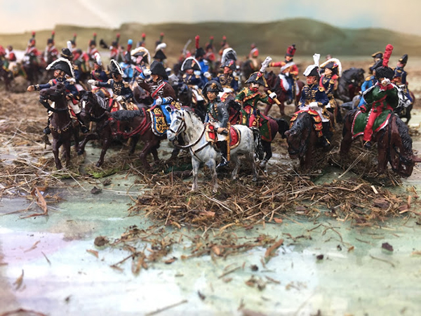 Several miniature painted French soldiers riding horses into battle