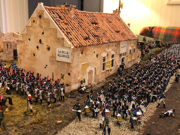Miniature French troops, some with drums or weapons, march in front of a tiny model of La Belle Alliance Inn
