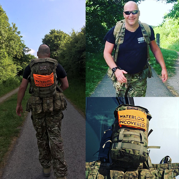 Veteran Ben Mead walking with a weighted pack as part of his two point six challenge, wearing camouflage with a large orange Waterloo Uncovered sign on his backpack
