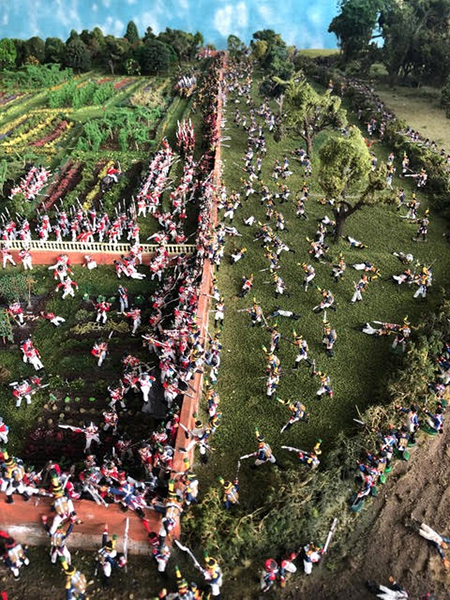 Hundreds of miniature military figurines fight in a miniature replica of the killing zone at Hougoumont, complete with a tiny fence, garden and trees