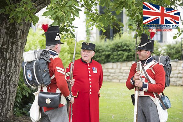 Chelsea Pensioner Trevor Rafferty stands in his Chelsea Pensioner uniform with two reenactors in Napoleonic British uniform.