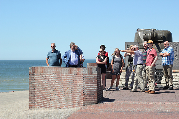 Participants of the 2019 Battlefields Uncovered Summer School standing in front of a war memorial on the coast during a field trip