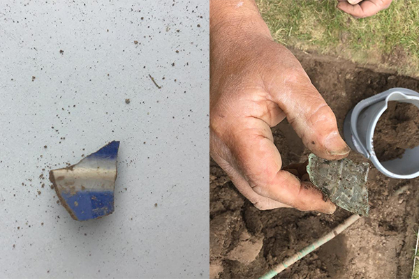 A piece of blue and white glazed pottery, and a piece of grey engraved pottery or brick, found in a test pit.