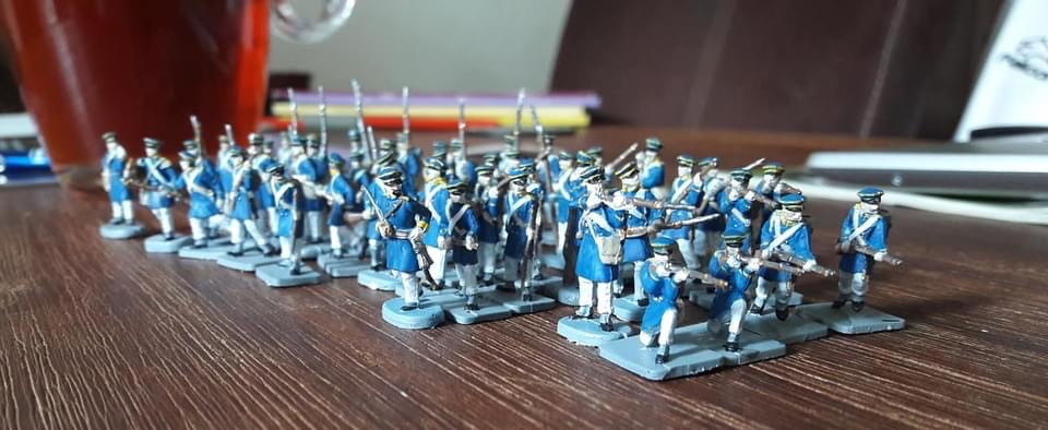 Around 50 small figurines of Prussian soldiers on a wooden table. The figurines are 20mm high and are painted in blue and white uniforms.