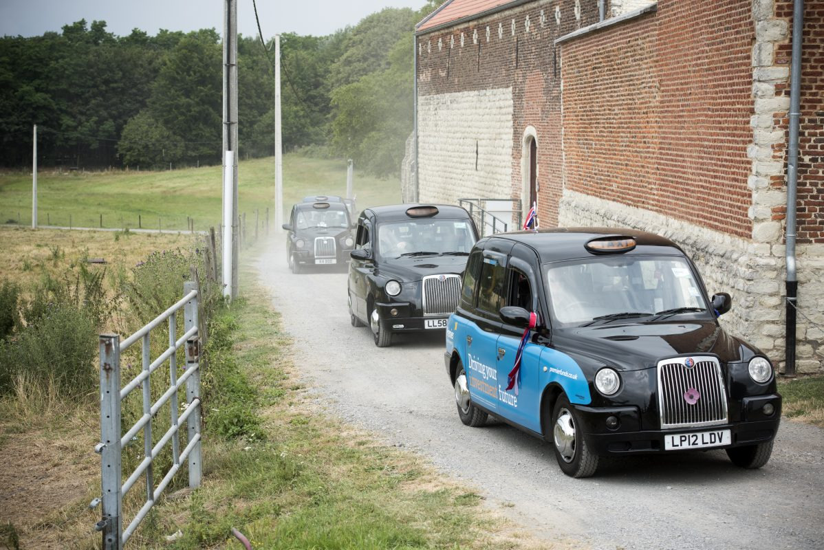 Four black cabs drive up the road to Hougoumont farm in a single file line.