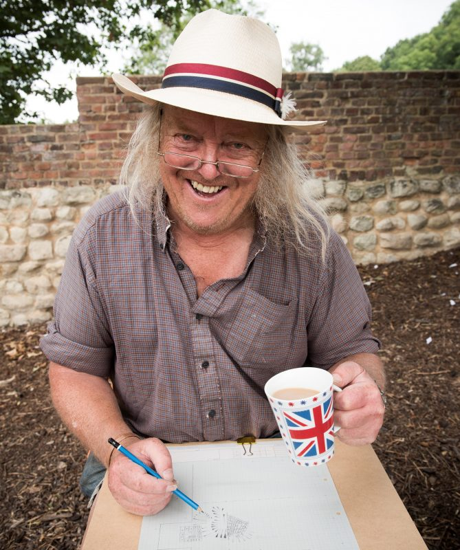 Archaeologist Phil Harding on site in 2019, drinking a cup of tea and drawing a plan of his trench.