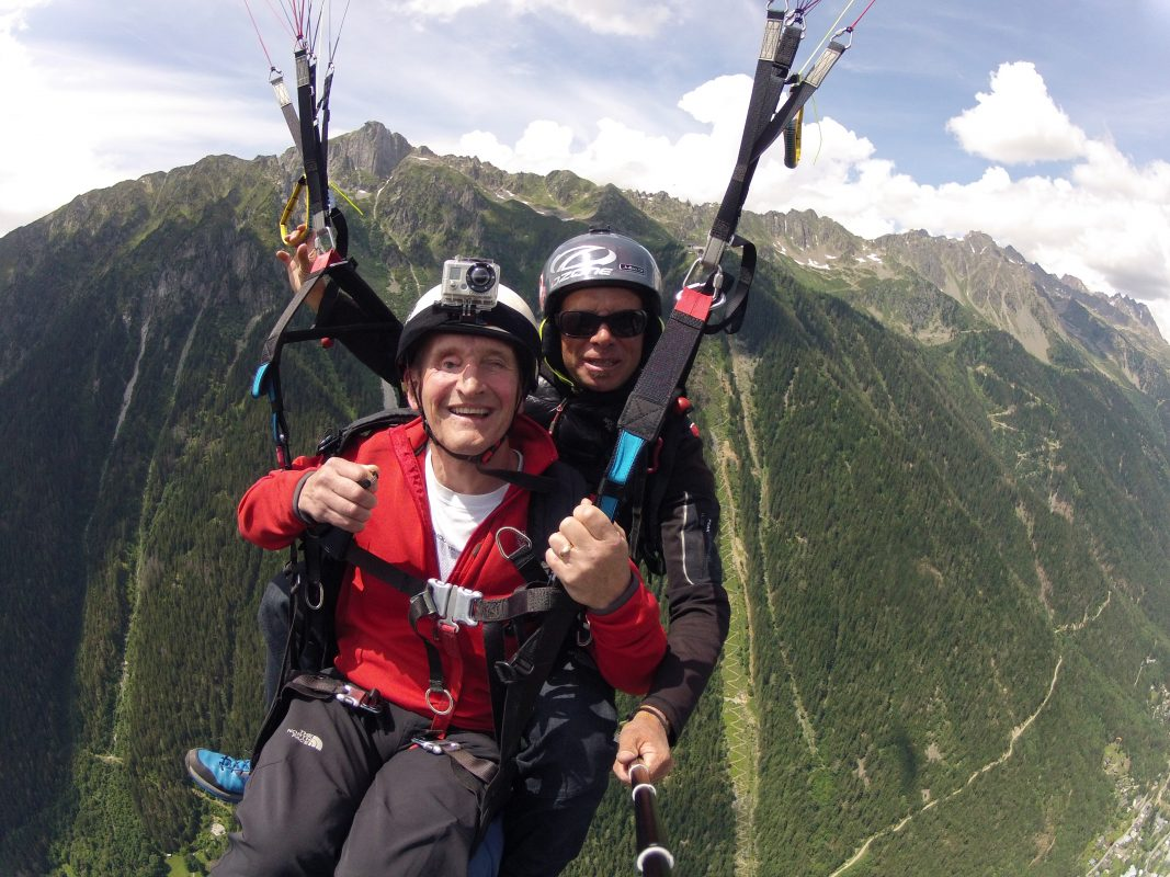 Jamie skydiving with an instructor over mountains.