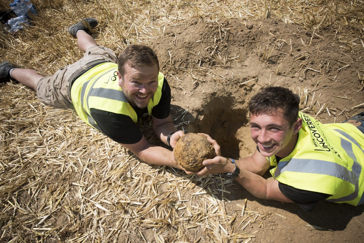 Alastair and Oliver lying on the floor holding a large round howitzer shell between them.