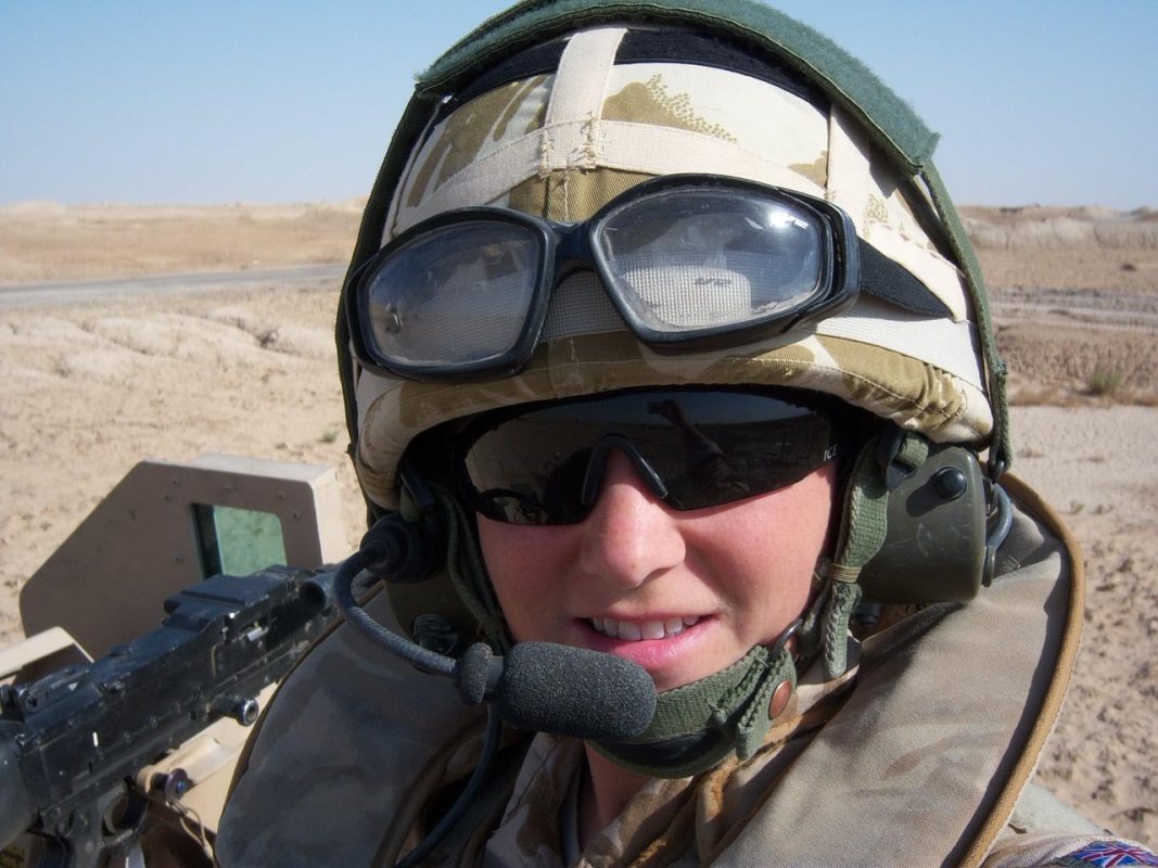 Jo in uniform in a desert while on tour in Iraq.