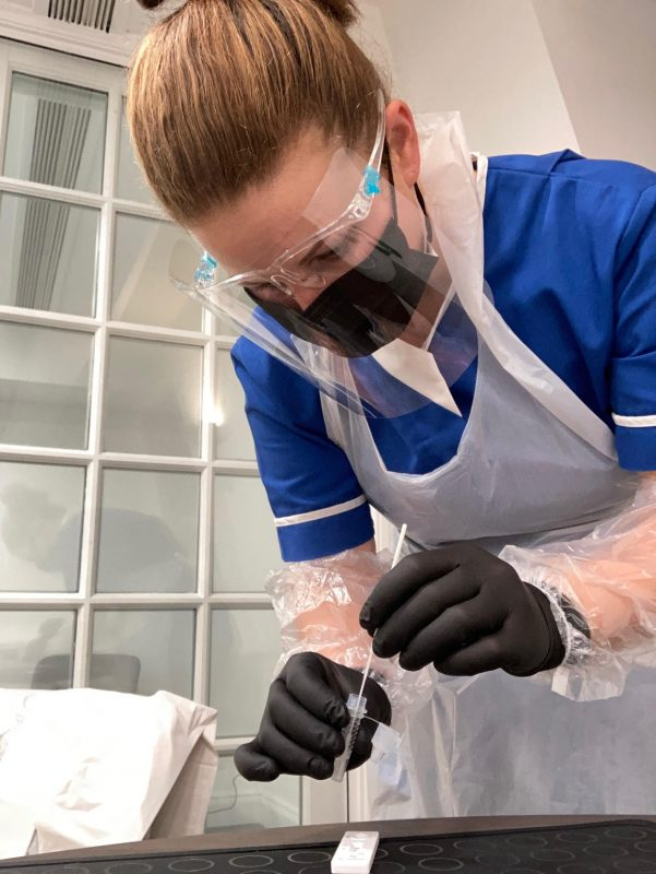 Jo in PPE including a mask, face shield and gloves with coronavirus testing equipment.