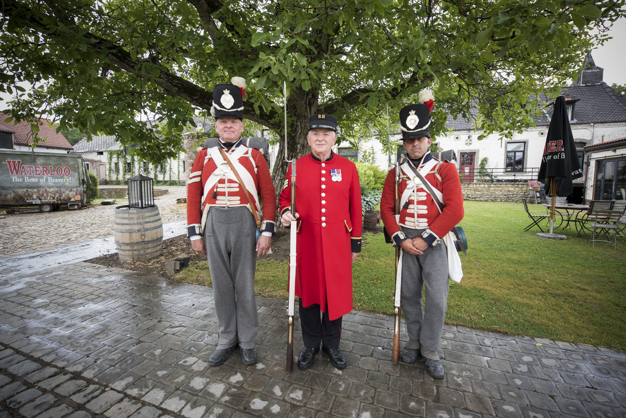 Two Coldstream Guards reenactors in red uniform stand with a Chelsea Pensioner in his red uniform in front of a tree