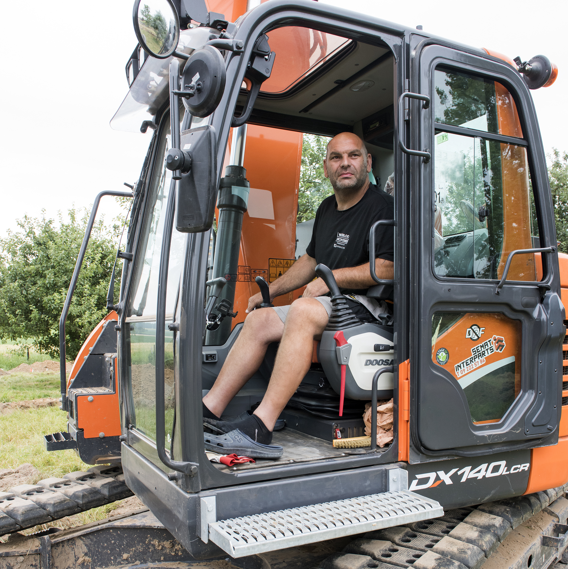 A digger driver sitting in the cab of an orange digger