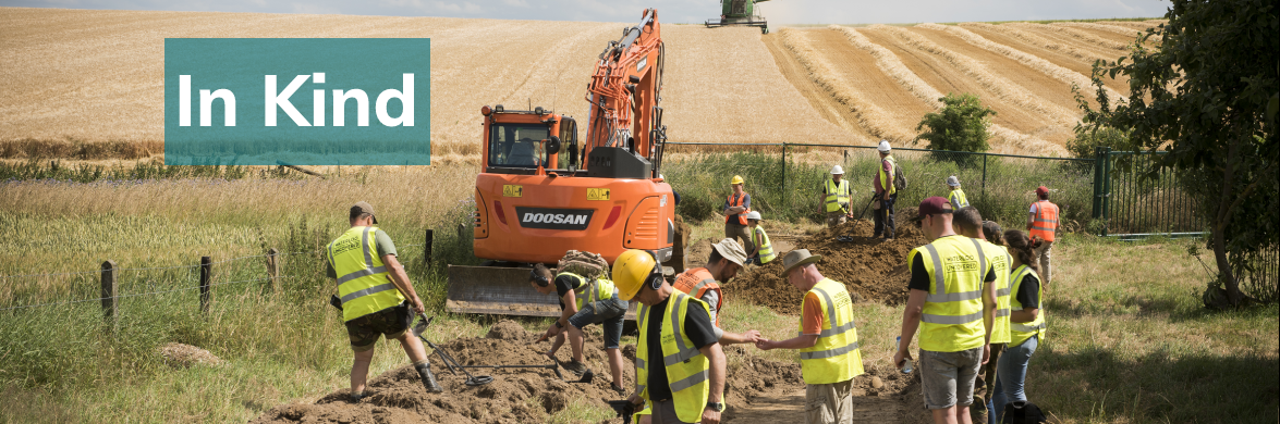 Veterans and archaeologists digging in front of a large orange digger. In Kind is written over the image.