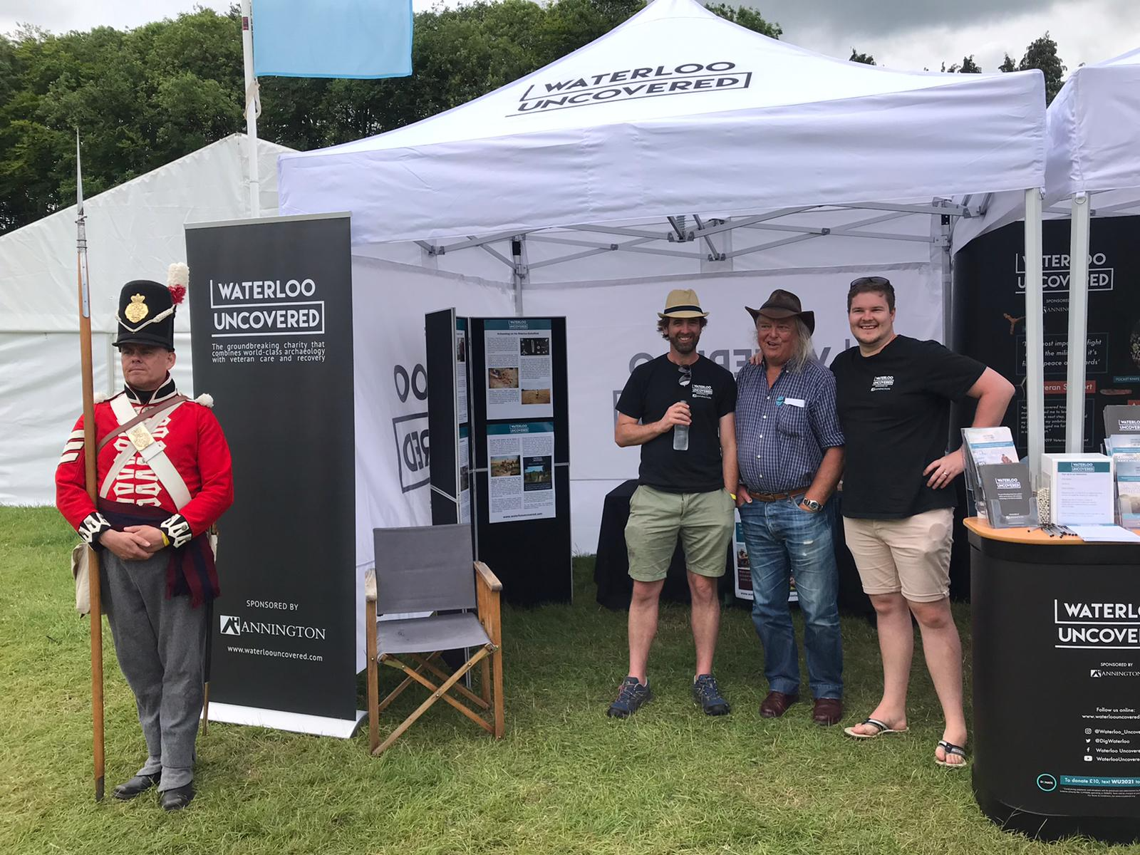 A Napoleonic reenactor, CEO Mark Evans, archaeologist Phil Harding, and web developer Sean Douglas in front of Waterloo Uncovered's stand at Chalke Valley history festival