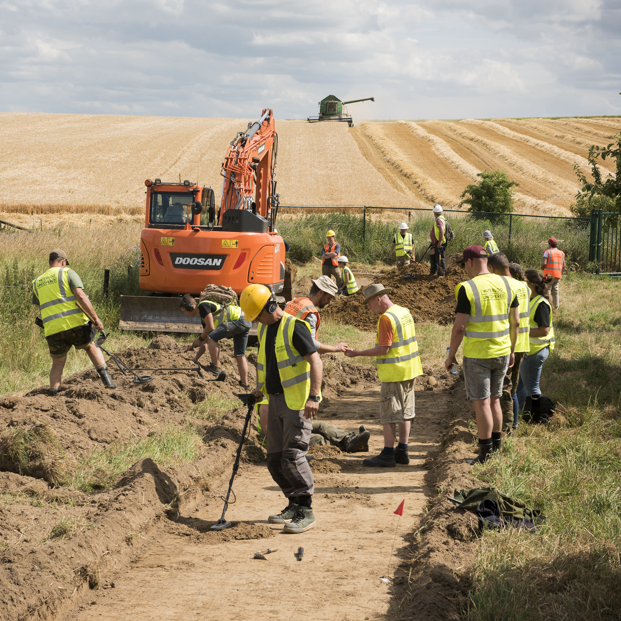 Veterans and archaeologists digging in front of a large orange digger.
