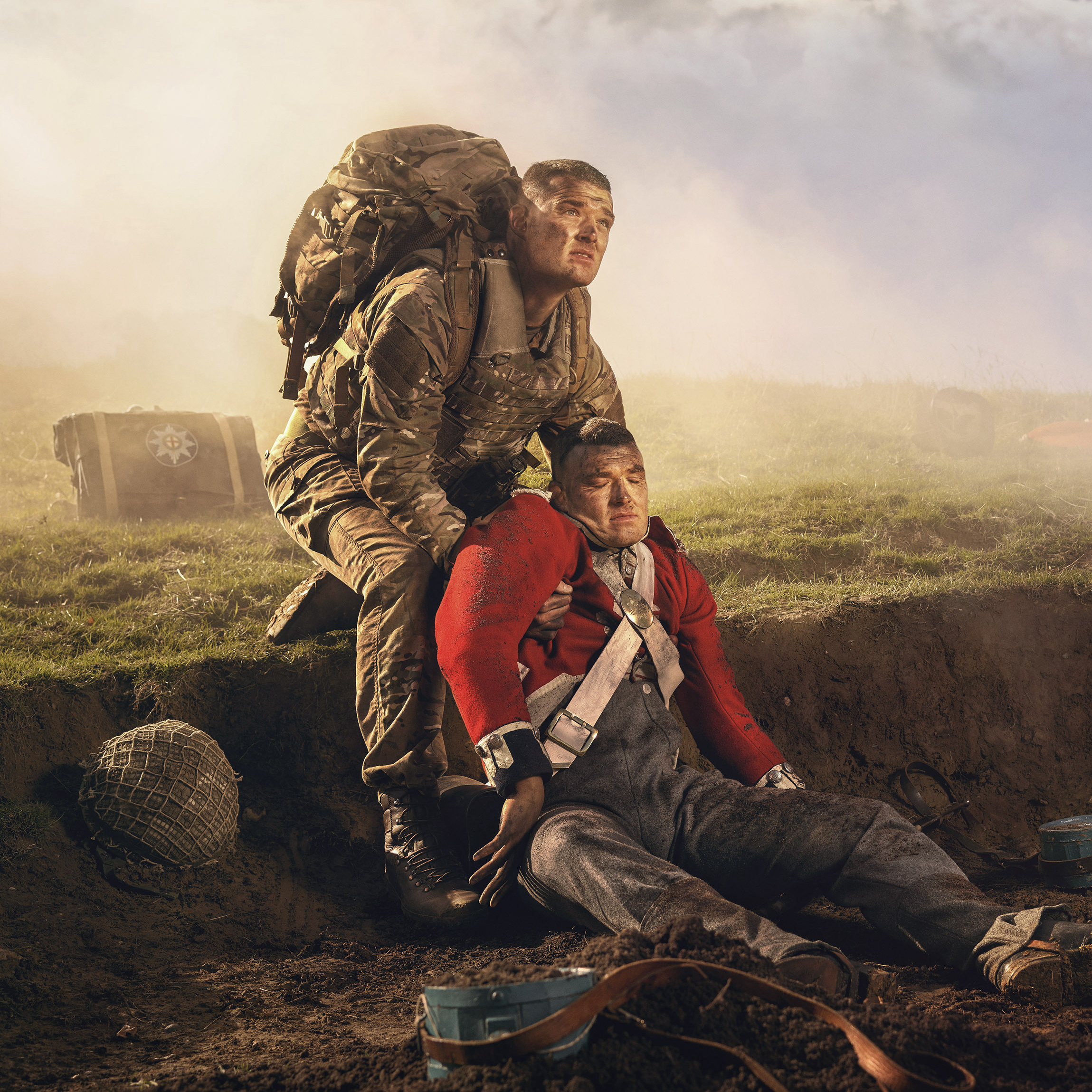 A modern day soldier supporting a Napoleonic soldier on the battlefield.
