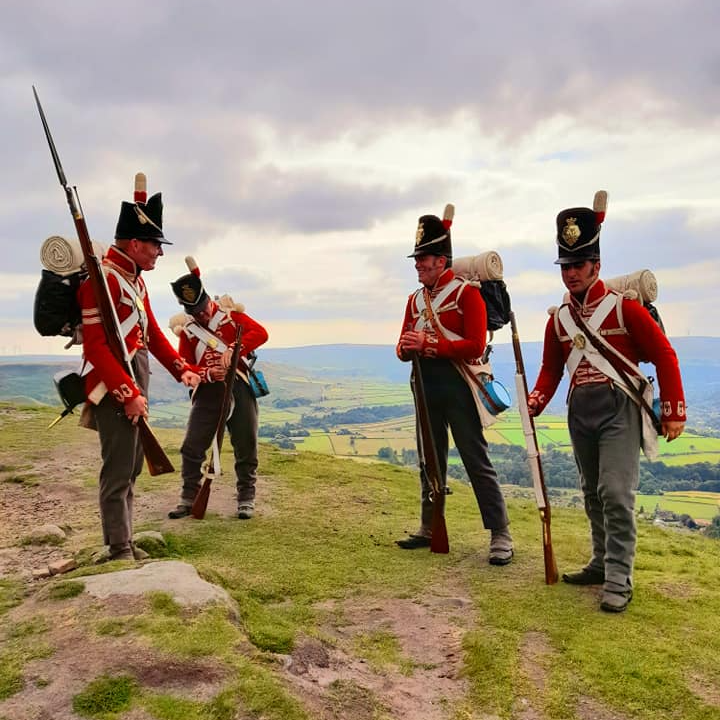 Four reenactors from His Majesty's 33rd Regiment of Foot stand on top of a hill with a view over the countryside